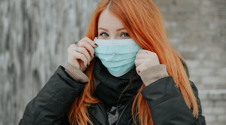 Redheaded woman with a surgical mask